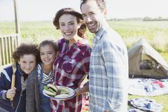 Portrait smiling family with barbecued hamburgers at sunny campsite - stock photo