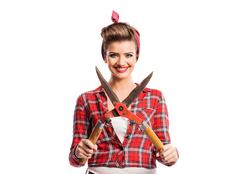Woman with pin-up make-up and hairstyle holding pruning shears - stock photo