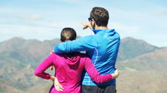 Young sporty couple hugging after hiking in the mountains Stock Footage