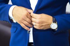 groom putting on cuff-links as he gets dressed in formal wear - stock photo
