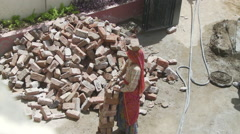 Women Laborer carrying bricks on head Stock Footage