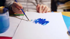 Child painting something on the paper using brush, steadycam shot Stock Footage