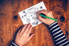 Female graphic designer sketching software icons on paper Stock Photos