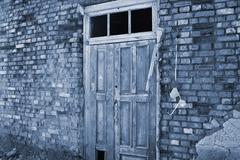 Old door on a dilapidated wall - stock photo