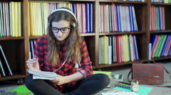 Student looking thoughtful and listening music in the library - stock footage