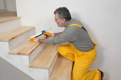 Home renovation, caulking wooden stairs with silicone Stock Photos