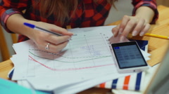 Student sitting in the library and doing homework on mathematics - stock footage