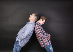 father and son lean on back to back - stock photo