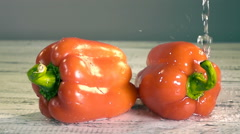 Water splashing on bell peppers in slow motion Stock Footage