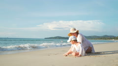 Mother With Little Son Resting On The Beach Near The Sea Stock Footage