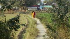 Two women walk down dirt path in bright colored saris. Stock Footage