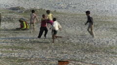 Children wrestle and play in Yamuna river bed near Taj Mahal Stock Footage