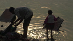 Man and child sort clothes to wash Stock Footage