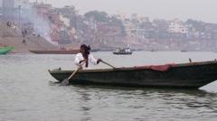 Man in boat rows toward shore Stock Footage