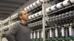 Engineer is Looking at the Machines in Textile Factory - stock photo