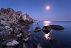 Seascape with moon and lunar path with rocks at night Stock Photos