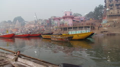 Rowing past Ghats and boats Stock Footage