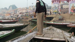 Man standing on the bow of a boat navigating through other moored boats. - stock footage