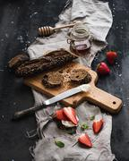 Breakfast set. Black baguette toasts with fresh strawberries, honey and masca - stock photo