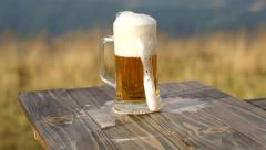 Glass of fresh beer on a table against the background of wheat fields Stock Footage