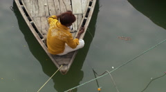 Boy fishing from bow of wooden boat from over he'd Stock Footage