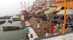 Woman and bathers on the bank of the ganges river getting dressed Stock Footage