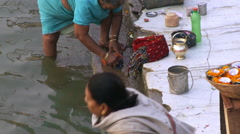 Close up view of woman pouring holy water into ganges river Stock Footage