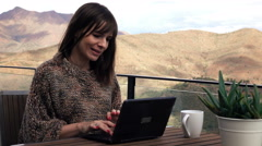 Young pretty woman sitting with laptop on terrace with mountains view, 4K Stock Footage