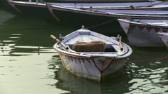 A small boat tied off to other boats. Stock Footage
