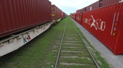 Aerial scene moving backwards through a train rail and flying over containers on - stock footage