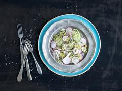 Spring salad with leek, radish and cucumber in vintage metal plate Stock Photos