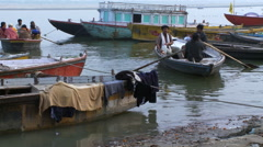 People in wooden boats near shore Stock Footage