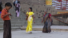 Shot following a group of well dressed people on steps of an Indian town. - stock footage