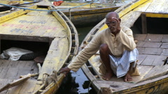 Old man with glasses and sarong sitting on boat Stock Footage