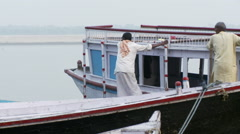 Two men guiding a boat out toward the water by hand. Stock Footage