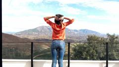 Young woman stretching arms while standing on terrace with mountains view, 4K Stock Footage