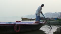 Older man on a boat navigating by the wharf. - stock footage