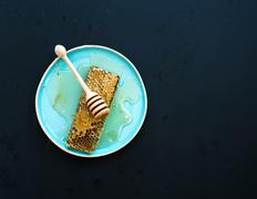Honeycomb with honey dipper on blue ceramic plate over black background, top  Stock Photos