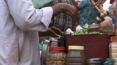Man cooking on street waves hand to get a sense of the aroma - stock footage