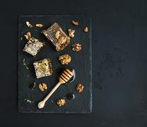 Honeycomb, walnuts and honey dipper on black slate tray over grunge dark back Stock Photos