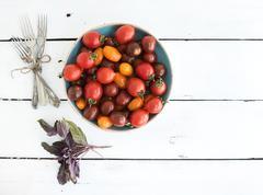 Cherry tomatoes in blue ceramic bowl, vintage silverware and fresh basil leav - stock photo