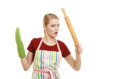 Funny housewife in kitchen apron holds baking rolling pin Stock Photos