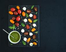 Caprese set. Cherry tomatoes of various color, mozarella, basil leaves, spice Stock Photos