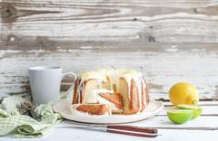 Moist lime and lemon bundt yoghurt cake, white rustic wooden  background. - stock photo