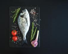Fresh uncooked dorado or sea bream fish with vegetables, herbs and spices on  Stock Photos