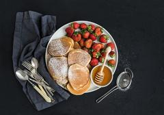 Breakfast plate. Homemade pancakes with fresh strawberry and honey, kitchen n - stock photo