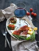 Wine appetizer set. Glass of red wine, vintage dinnerware, brushetta with che - stock photo