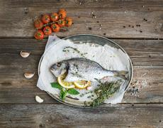 Roasted dorado or sea bream fish with vegetables, herbs and spices on silver  Stock Photos