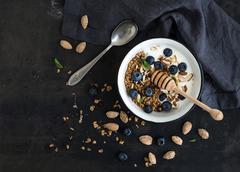 Healthy breakfast. Oat granola with fresh blueberries, almond, yogurt and min - stock photo