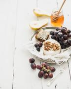Camembert cheese with grape, walnuts, pear and honey on vintage metal plate o - stock photo